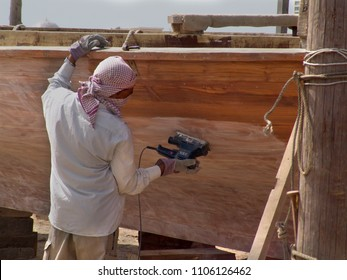 Abu Dhabi, United Arab Emirates - April 11, 2004: worker at a traditional shipyard polishes a wooden Arabian dhow with a machine