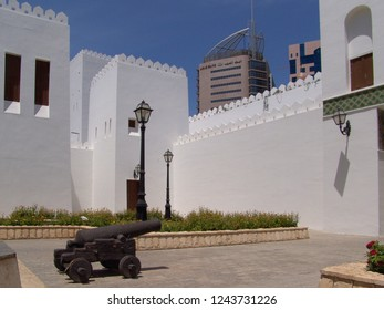 Abu Dhabi, United Arab Emirates - April 11, 2004: old cannon in front of walls and towers of Qasr al Hosn, the white fort at a sunny day with blue sky, building of Arab Bank is in background