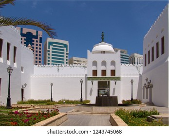 Abu Dhabi, United Arab Emirates - April 11, 2004: walls and gate of historic white fort, qasr al hosn, behind a yard on a sunny day with blue sky, tall modern buildings can be seen in background