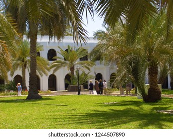 Abu Dhabi, United Arab Emirates - April 11, 2004: beautiful garden with green lawn and palms in a yard of the white fort qasr al hosn
