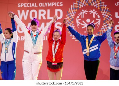 Abu Dhabi, United Arab Emirates - March 20, 2019:  Gymnastic athletes cheer during decoration ceremony during Special Olympics World Games in Abu Dhabi National Exhibition Centre.