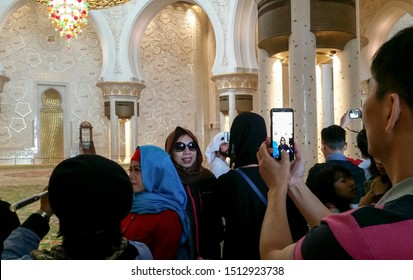 Abu Dhabi, United Arab Emirates, February 7, 2019: Asian tourists are visiting the interior of the Sheikh Zayed Grand Mosque, photographing each other.