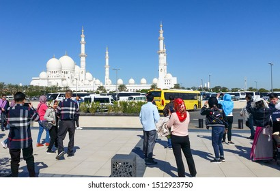 Abu Dhabi, United Arab Emirates, February 7, 2019: Asian tourists arrive at the parking place of the Sheikh Zayed Grand Mosque in Abu Dhabi and photographing the mosque.