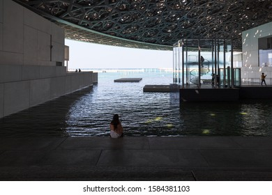 ABU DHABI, UNITED ARAB EMIRATES - NOVEMBER 27, 2019: Girl tourist stands on the background of the Louvre Abu Dhabi. Louvre is a new museum in United Arab Emirates opened on November 8th 2017