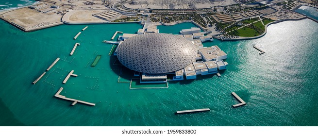 Abu Dhabi, United Arab Emirates - April 6, 2021: Panoramic aerial view of Louvre museum in Abu Dhabi emirate of the United Arab Emirates at sunrise. View of the building appear to float on the seaside