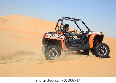 ABU DHABI, UNITED ARAB EMIRATES - DEC 27, 2015: People in dune buggy racing across desert landscape.