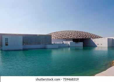 "Abu Dhabi, United Arab Emirates, November 14, 2017: Louvre Abu Dhabi. View of the Louvre, across water, showing the ""Rain of Light"" Dome."