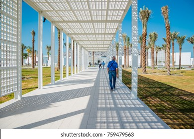 Abu Dhabi, United Arab Emirates, November 14, 2017: Louvre Abu Dhabi. Man walking down the path towards the Louvre.