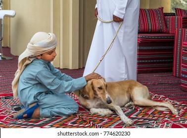 Abu Dhabi, United Arab Emirates, December 8th, 2017: Arab kid with saluki dog