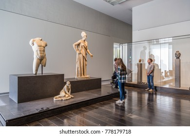 Abu Dhabi, United Arab,  Emirates, December 5, 2017: The Louvre. Visitors looking at Greek and Roman sculptures dating from the 5th century BC, on loan from the Louvre, Paris.