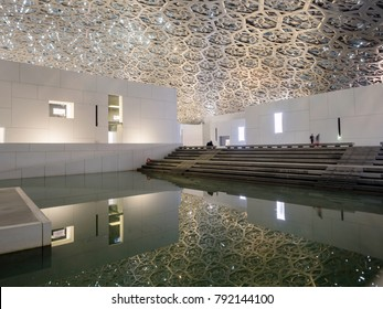 Abu Dhabi, United Arab Emirates - December 20, 2017: The Louvre museum with modern design exterior luminated at night