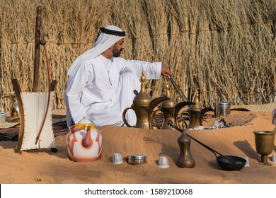 Abu Dhabi/UAE - December 14 2019: Al Hosn Heritage Festival, Emirati man seating in fron of open fire and making traditional coffee Gahwa