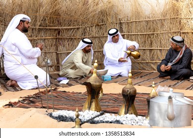Abu Dhabi/UAE - January 12 2019: Arabic men gather together and drink coffee seating in traditional Bedouin tent. Arabic hospitality concept