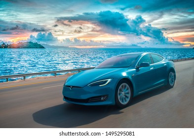 Abudhabi,UAE on 27-11-2018.A rare blue coloured tesla model s drives on a beach side abudhabi road.There is a sunset behind the ocean.