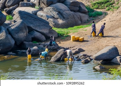 Abuja, Nigeria - March 13, 2014: Unidentified young children filling yellow water containers at river
