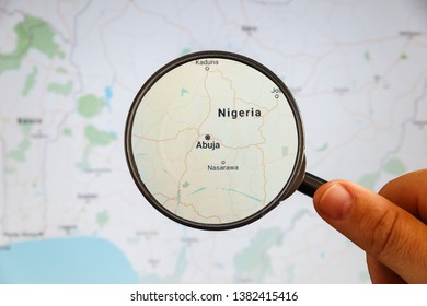 Abuja, Nigeria. Political map. City visualization illustrative concept on display screen through magnifying glass in the hand.