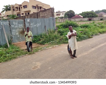 Abuja, Nigeria-May 9,2013-Two small boys, living in poverty,  take a break from playing with their motorcycle tires and sticks in the Maitama District of Abuja, Nigeria