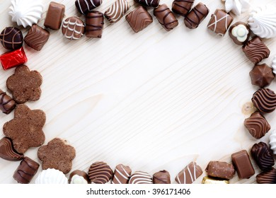 abundance of chocolates, meringue and cookies of handwork on a light wooden background in the form of a frame, close up, the top view