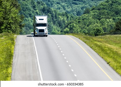 An abundance of copy space.anchored by a white eighteen-wheeler coming towards the camera.  Heat waves from the highway create a nice shimmering effect on the truck and background.