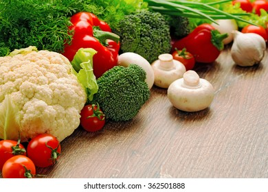 Abundance of fresh vegetables and greens on a dining wooden table. Cauliflower, broccoli, cherry tomatoes, paprika, green onions, garlic, lettuce leaves, fennel, champignon mushrooms close up