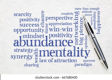 abundance mentality word cloud on a textured lokta paper wit a pen