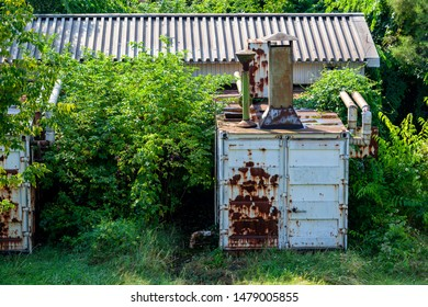 Abundant industrial ruins are overgrown in a remote area.