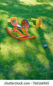 Abundantly decorated red rocking horse with small warn chair and ball. Desolated toys on green grass background with shadows