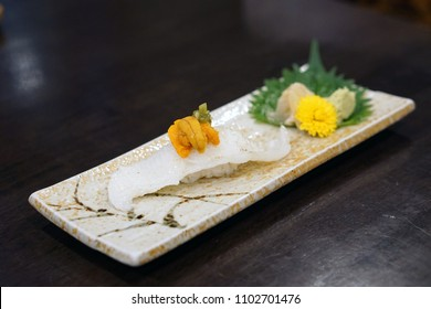 Aburi engawa sushi, Grilled flatfish (Fluke fin) on rice topping with fresh uni served with pickled ginger, Japanese traditional food.