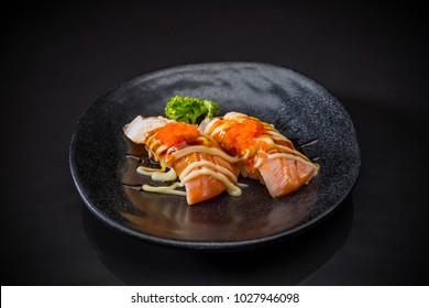 Aburi Salmon Nigiri, Sushi salmon burned and topped with Shrimp Eggs, mayonnaise served on traditional Japanese food on ceramic dish, Japanese food style, Japanese menu, selective focus
