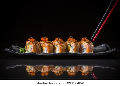Aburi, Salmon Roll topped Foie Gras Roll served on long dish, Japanese food style, Sushi Menu, salmon sushi roll on black background, selective focus