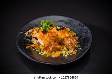Aburi Spicy Salmon Nigiri, Burned Salmon Sushi and topped with Shrimp Eggs, tempura and spicy sauce served on traditional Japanese food on ceramic dish, Japanese food style,  selective focus