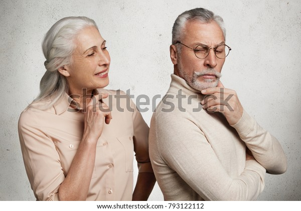 Abused angry elderly man in eyewear stands back to his wife, being upset after quarrel, have some misunderstanding between each other, isolated over grey concrete wall. Mature couple poses indoor