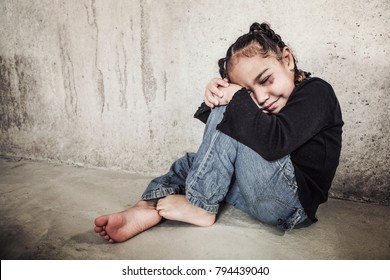 Abused child with eyes closed hiding next to a wall