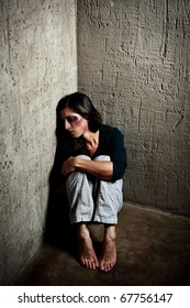 Abused woman in the corner of a stairway comforting herself after getting hit by her husband