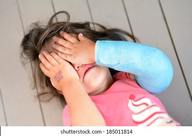 Abused young girl(age 3-4) with a broken arm covering here face while crying. Concept photo of child abuse, violent in the family,domestic violent, social issues.Real people. Copy space