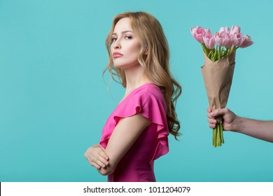 Abused young woman is turning back to male hand holding flowers. Apology concept. Isolated and copy space
