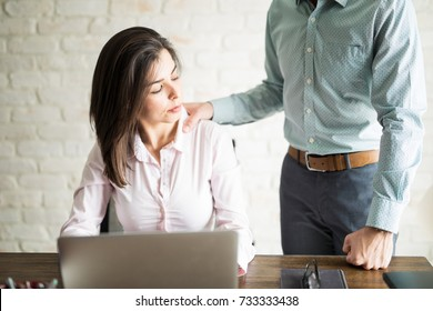 Abusive boss harassing a female colleague in the office while she looks uncomfortable and upset
