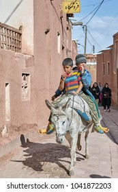 Abyaneh, Iran - April 26, 2017: Two Iranian boys ride on a donkey through a narrow street in the traditional village in the mountains.