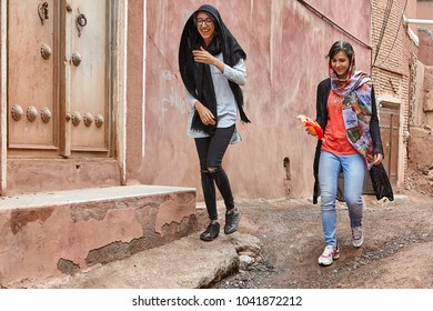 Abyaneh, Iran - April 26, 2017: two young women in hijabs are walking along a narrow street in the traditional village in the mountains and laughing.