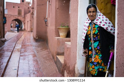 ABYANEH, IRAN - February, 2019: lady in traditional clothes in the ancient village of Abyaneh, near Kashan, in Iran. In background, the typical red mud-brick houses of Abyaneh.