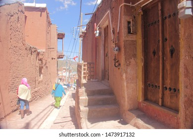 Abyaneh Village, Iran - April 22 2019 : An alley with reddish hue brick house facade in Abyaneh Village which is the oldest Iranian traditional village in Isfahan Province, Iran.