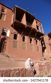 Abyaneh Village, Isfahan, Iran - October 2017 : Old local Iranian woman in colorful scarf sitting in front of her reddish hue home in one of the oldest village in Iran.