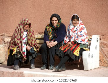 Abyaneh,Iran,10 mar 2019:3 women wearing  colorful floral hijab headdress,sitting on concrete in Abyaneh Village, Iranian historical village,located near Karkas Mountain in Natanz, Isfahan,Middle East