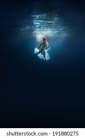 Abyss. Young redhead woman underwater