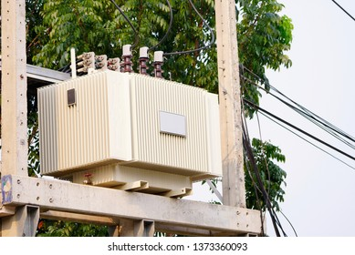 AC high-voltage power transformer. Electrical energy transfer to end users through distribution transformer on concrete pole changing high voltage to low voltage in Thailand.
