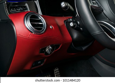 AC Ventilation Deck in Luxury modern Car Interior. Modern car interior details with red and black leather with red stitching. Carbon panel. Perforated leather steering wheel