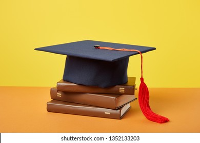 Academic cap and brown books on orange surface isolated on yellow