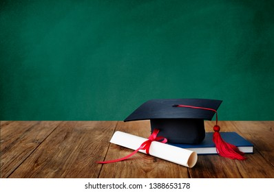 Academic cap, graduation diploma and a book in  front of the green chalkboard