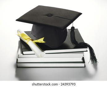 Academic cap with tassel and diploma on stack of books.