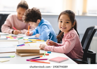 Academic Concept. Smiling junior asian school girl sitting at desk in classroom, writing in notebook, posing and looking at camera. Group of diverse classmates studying in the background